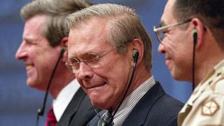 Donald Rumsfeld grimaces while listening to a translation