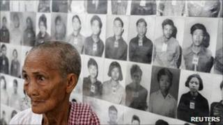 A survivor of the Khmer Rouge regime stands in front of portraits of victims at the Tuol Sleng (S-21) genocide museum in Phnom Penh