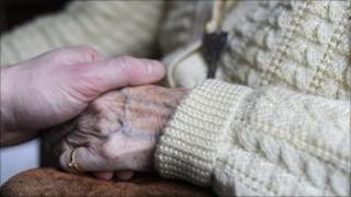 A close-up picture of a carer reaching out to hold the hand of an elderly person in a cardigan