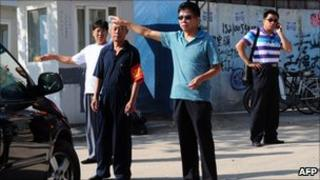 Plainclothes police direct a vehicle away from the home of freed dissident Hu Jia on outskirts of Beijing on 26 June 2011