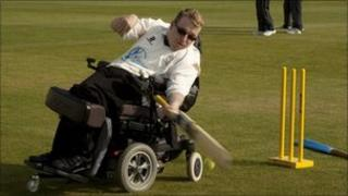 A man in a wheelchair playing cricket