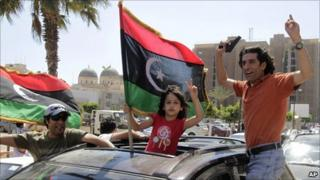 Supporters of the rebels wave guns and pre-Gaddafi Libyan flags in Benghazi after an arrest warrant is issued for Muammar Gaddafi (27 June 2011)