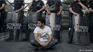 A protester sits in front of riot police during a peaceful ongoing rally against plans for new austerity measures