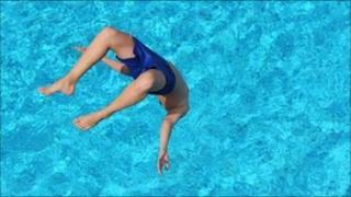 Boy jumps in a pool