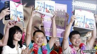 Tourists from Xiamen, China, accept gift packages as they arrive in Taipei