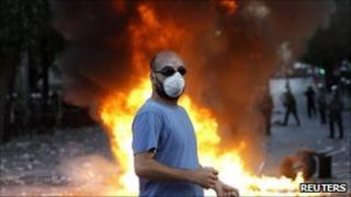 Protester stands before a fire on Syntagma Square in Athens