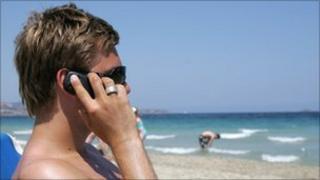 Man talking on phone on beach