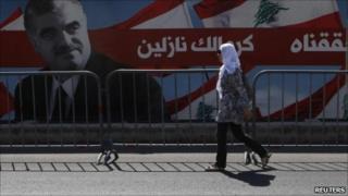 Beirut - Woman walks in front of Hariri poster. 30 June 2011