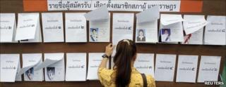 A woman checks a list before casting her ballot at a polling station in Bangkok, June 26, 2011