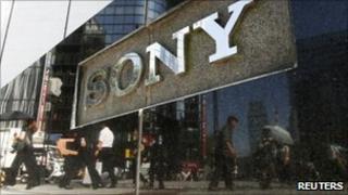 Pedestrians walk past a Sony sign in Tokyo