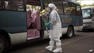 A Japanese evacuee, wearing a suit to protect him against radiation, boards a bus Minamisoma to take him to his home village of Namie inside the nuclear exclusion zone - 27 May 2011