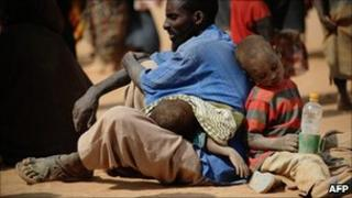 A Somali man who fled violence and drought in Somalia with his family sits on the ground outside a food distribution point in the Dadaab refugee camp in north-eastern Kenya on 5 July 2011