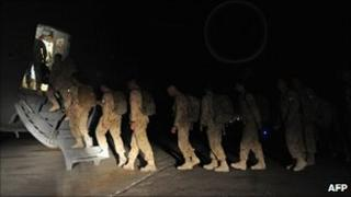 Canadian soldiers walk to board a plane on their way home at Kandahar airbase on July 5, 2011