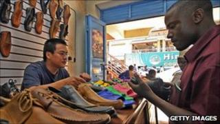 A Ugandan browses at shoes in a Chinese-owned shop in Kampala (archive shot)