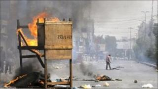 Pakistani protesters burn material in the middle of a street in a violence-hit western neighbourhood of Karachi on 8 July 2011