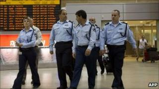 Israeli police walk past airport arrivals board.