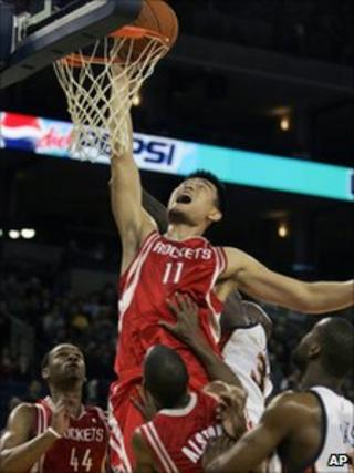 Yao Ming dunking a basketball and scoring against the Golden State Warriors in 2006
