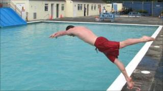 A swimmer dives into Hayle's pool