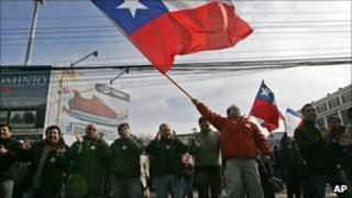 A worker from Chile's state-owned copper mining company Codelco, waves a Chilean flag next to co-workers during a strike in Los Andes, Chile, 11 July 2011.