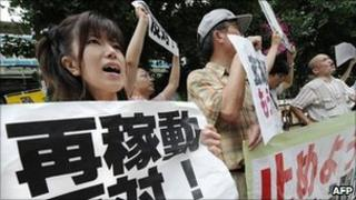 People shout slogans as they hold banners during an anti-nuclear power plant rally in front of the Tokyo office of Kyushu Electric Power Co, in Tokyo on July 8, 2011