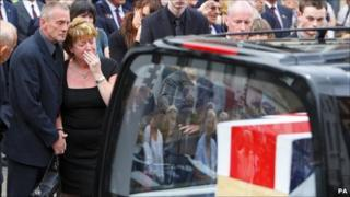 Family members beside the hearse
