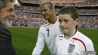 England mascot Robert Sebbage (R) watches Brazil's President Luiz Inacio Lula da Silva (2nd L) greet England's David Beckham