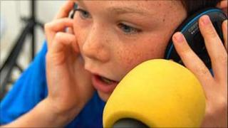 Visitor to the BBC East Midlands roadshow has a go at reading the news in 2009