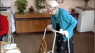 Elderly woman uses walking aid