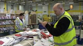 Postal workers sorting mail