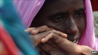 A displaced Somali woman cries after one of her children died of malnutrition at a camp near Mogadishu airport