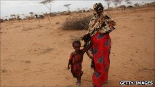 A woman walks with a child on the outskirts in the Dagahaley refugee camp which makes up part of the giant Dadaab refugee settlement on July 19, 2011 in Dadaab, Kenya