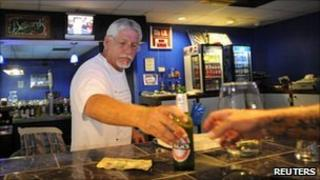 Business owner Stephen Gaughran (C) sells a beer to a regular customer from behind the bar inside his billiard hall in Titusville, Florida July 6, 2011
