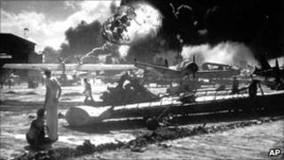 US soldiers standing near burning military aircraft during the Japanese attack on Pearl Harbor in 1941