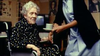A nurse helping an elderly woman in a wheelchair