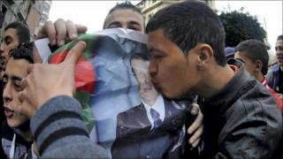 A man kissing a poster of Algeria's leader