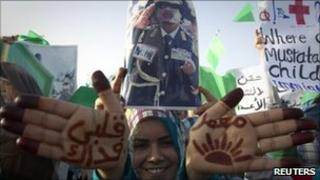 """A pro-Gaddafi demonstrator shows script on her hands reading """"I'll sacrifice my life for Muammar"""" in Sirte, the hometown of Libyan leader Col Gaddafi, on 21 July."""