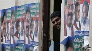 "A Sri Lankan ethnic Tamil man peeps from between a wall pasted with election propaganda of Sri Lankan president Mahinda Rajapaksa""s ruling party, in Jaffna, Sri Lanka, Friday, July 22, 2011"