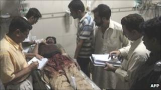Paramedics treat an injured man in a Karachi hospital