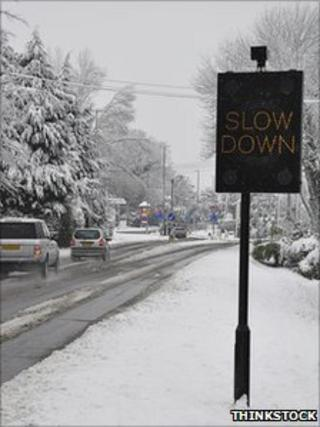 Slow down sign in snow (Thinkstock)