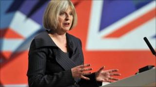 Theresa May speaking with a union flag behind her