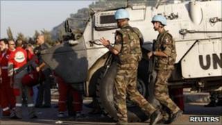UN peacekeepers next to blast-damaged vehicle.