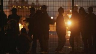 Asylum seekers standing at the port of Calais, France