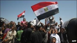 People watching the trial of Hosni Mubarak on an outdoor TV screen in Cairo