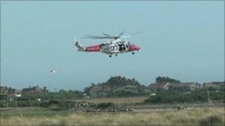 Solent Coastguard helicopter rescuing a cyclist who got stuck in mudflats at East Head, Chichester Harbour, West Sussex in July last year