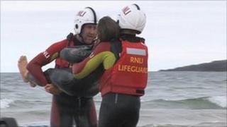 Lifeguards demonstrate how to remove a swimmer from the water