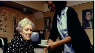 An old lady getting a cup of tea from a carer