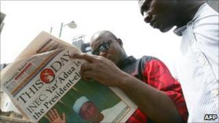 Nigerians reading a newspaper