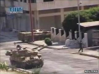 A soldier walks near an army tank on a street purportedly in Hama (Still image taken from amateur video on 7 August 2011)