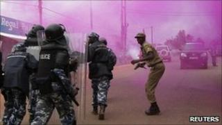 Riot policemen run through a cloud of coloured teargas to disperse supporters of Uganda's opposition marching on a street in Masaka town, 120 km (72 miles) southwest of the capital Kampala August 10, 2011.