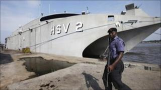A Nigerian naval officer walks past a US high speed vessel during a maritime conference